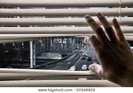 Man at office opening window blinds and seeing city streets and buildings