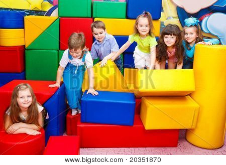 Group of joyful kids playing with large leather blocks