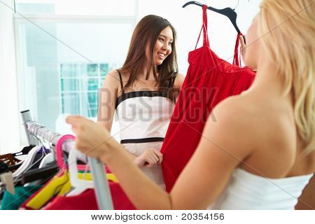 Image of pretty females looking at smart dress while choosing a right one