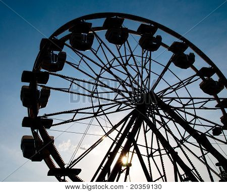 Silhouette of ferris wheel at county fair.