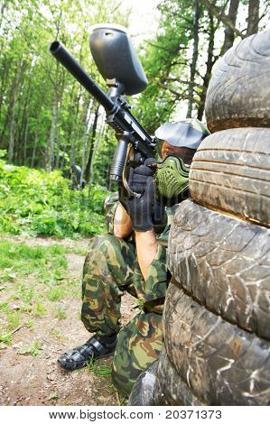 paintball sport player in protective uniform and mask making gunfire to enemy from shelter outdoors