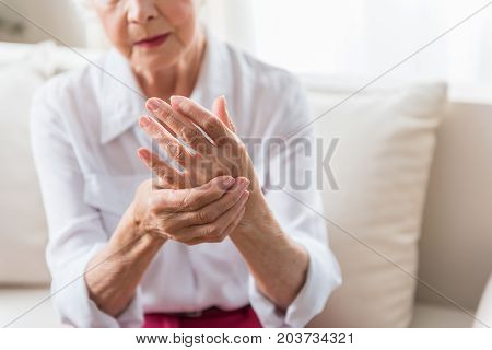 poster of Arthritis. Close-up of hands of unhappy senior lady is feeling arm ache and expressing suffering. Copy space in the right side