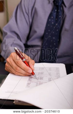 businessman is filling in the tax form