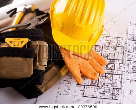 set of tools and constuction plans with yellow helmet