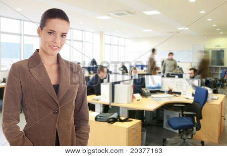 businesswoman standing at the busy office