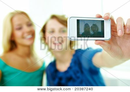 Happy girls taking photo of themselves on telephone camera