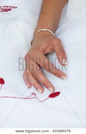 Lady's Hand auf weichen weißen und roten material