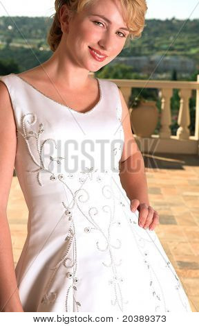Young blond bride with short hair in embellished gown standing on the balcony