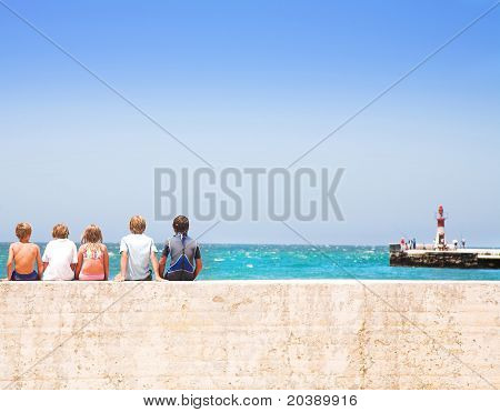 Children sitting on the wall with their backs to camera, watching sea near lighthouse