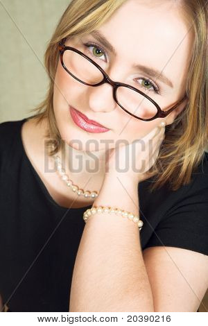 Young blond woman wearing glasses with tired expression on her face, rubbing her neck