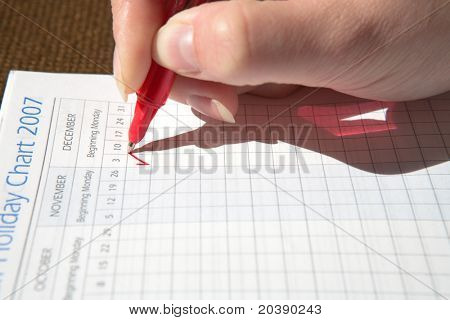 Woman marking a holiday date in a diary with red pen, focus on the red mark