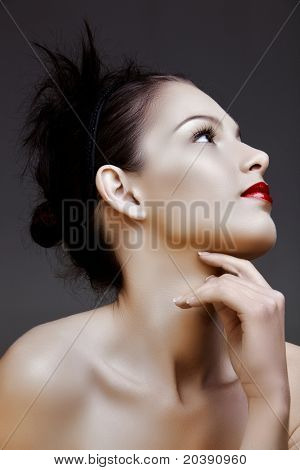 beautiful woman with red lips and hair in knot, resting on her hand