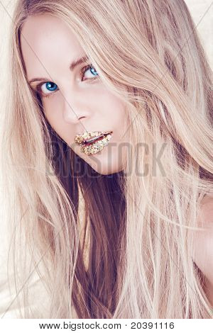 beautiful woman with long blond hair and blue eyes with artistic gold leaf lips