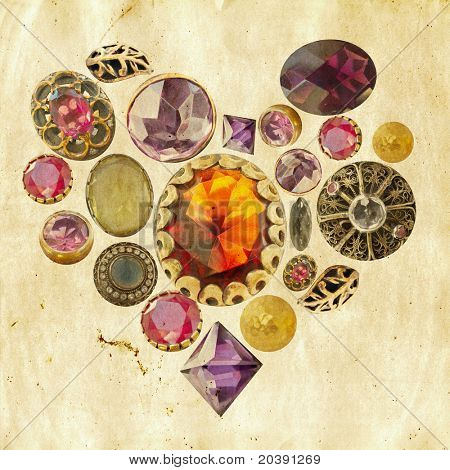 gems and precious stones arranged in heart shape on grunge paper background