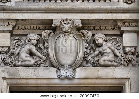 Detail on a door of the Grand Palais in Paris with a bas-relief medallion and two cherubs
