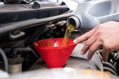 Mechanic Pouring Oil To Vehicle Engine. Serviceman Changing Motor Oil In Automobile Repair Service. poster