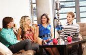stock photo of hookah  - Group of young and sexy people smoking hookah in the lounge caffee - JPG