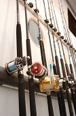 stock photo of fishing rod  - Deep Sea fishing poles lined up on the side of a boat - JPG