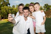 picture of family fun  - father taking a photo of whole family at the park on a sunny day - JPG
