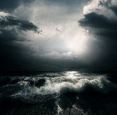 Dark storm clouds and huge waves on a sea