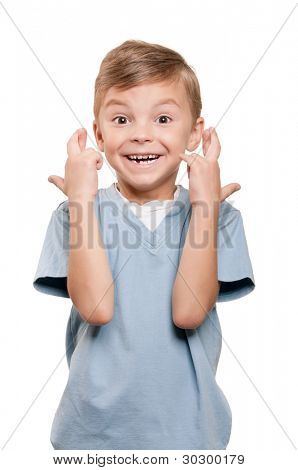 Portrait of superstitious little boywith crossed fingers over white background