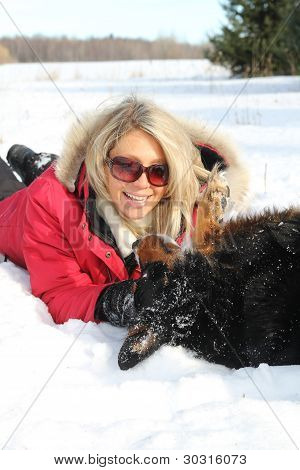 Woman Playing With Dog In Winter