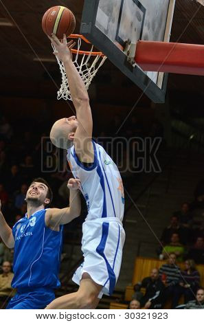 KAPOSVAR, HUNGARY – FEBRUARY 18: Gergely David (in white) in action at a Hungarian Championship basketball game with Kaposvar (white) vs. Fehervar (blue) on February 18, 2012 in Kaposvar, Hungary.