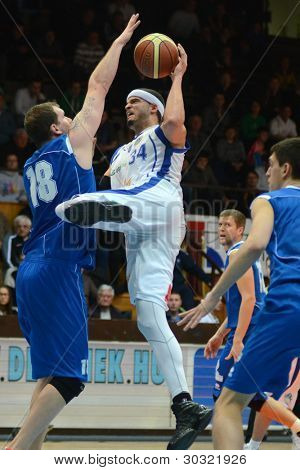 KAPOSVAR, HUNGARY - FEBRUARY 18: Michael Fey (in white) in action at a Hungarian Championship basketball game with Kaposvar (white) vs. Fehervar (blue) on February 18, 2012 in Kaposvar, Hungary.