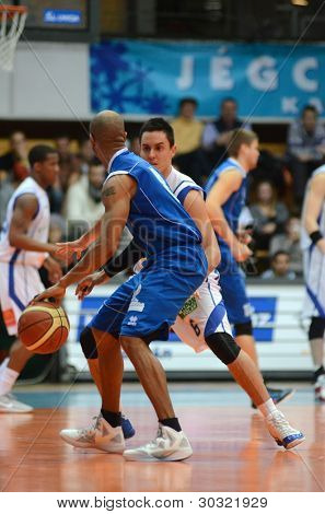 KAPOSVAR, HUNGARY – FEBRUARY 18: Kornel Kiss (in white) in action at a Hungarian Championship basketball game with Kaposvar (white) vs. Fehervar (blue) on February 18, 2012 in Kaposvar, Hungary.