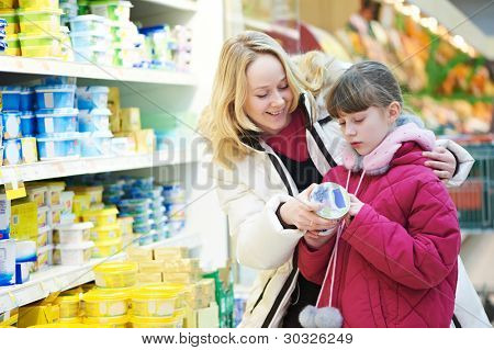 woman and girl choosing produces in dairy shopping mall