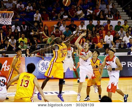 KUALA LUMPUR - FEBRUARY 19: Slingers L. Graham (24) tries to block Dragons Ernani Pacana's (22) shot at an ASEAN Basketball League match on February 19, 2012 in Kuala Lumpur. Dragons won 86-71.