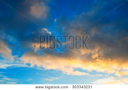 poster of Sunset colorful sky background - pink, orange and blue dramatic colorful clouds lit by evening sunshine. Vast sunset sky landscape
