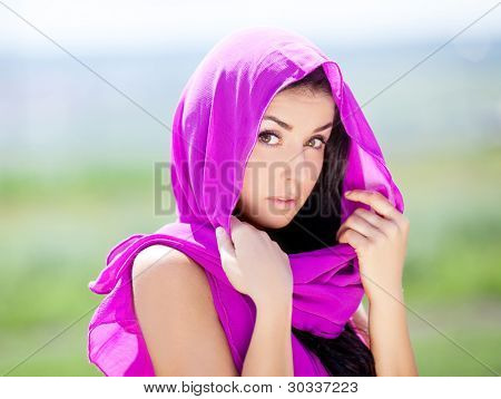 beautiful young brunette oriental beautiful woman, wearing pink clothes and a shawl outdoor on a summer day