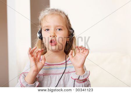 Singing little child with headphone at hame