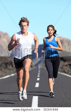 Running couple. Runners outdoor jogging workout on road beautiful landscape. Fit athletes training, Caucasian man, Asian woman.