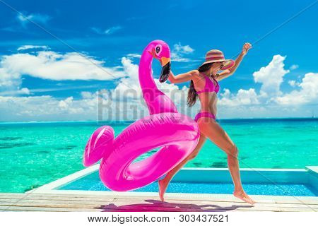poster of Vacation fun woman in bikini with funny inflatable pink flamingo pool float running of joy jumping b