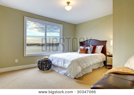 Green Large Bedroom With White Bed And Water View.