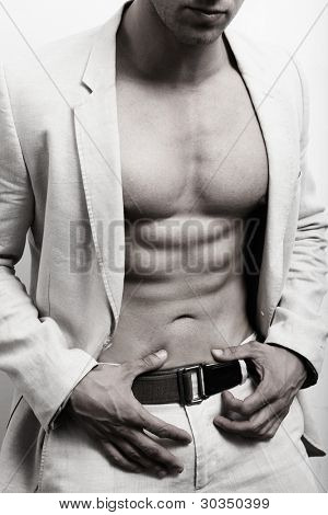 Muscular man with sexy abs and suit over white wall