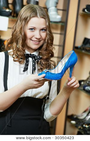 Young woman choosing shoes during footwear shopping at shoe shop