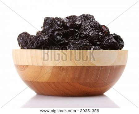 yummy dried plums in wooden bowl isolated on white
