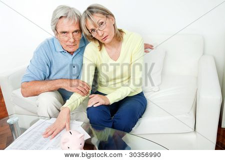 Worried senior couple with bills and piggy bank in living room