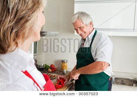 Senior man cutting pepper for cooking in kitchen