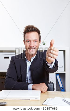 Happy successful business man in office holding thumbs up