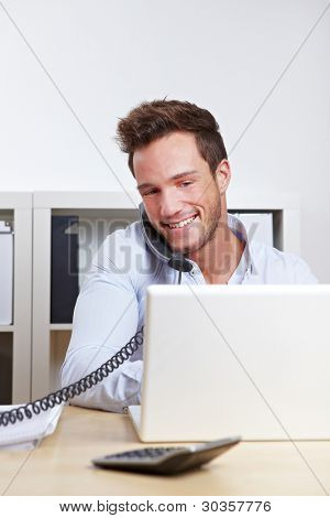 Happy young business in office making a phone call