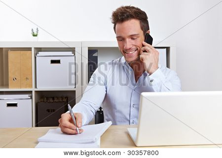 Smiling business man using cell phone at desk in office