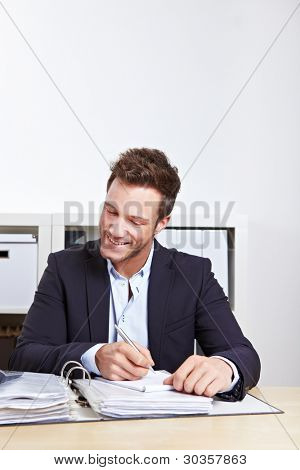 Happy business man taking notes in files in office