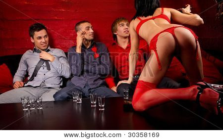 Three men drinking and looking at dancing woman.