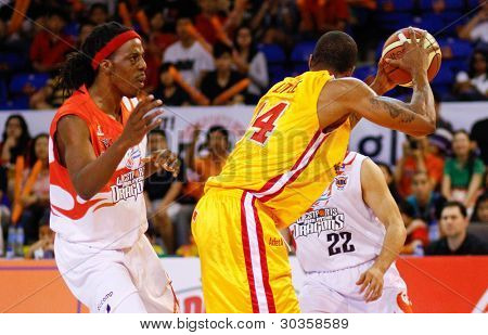 KUALA LUMPUR - FEBRUARY 19: Slingers' Donald Little (14) shields the ball from Tiras Wade of the Dragons at the ASEAN Basketball League match on February 19, 2012 in Kuala Lumpur, Malaysia. Dragons won 86-71.