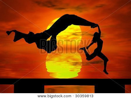 Silhouette of a  woman jumping at the sunset