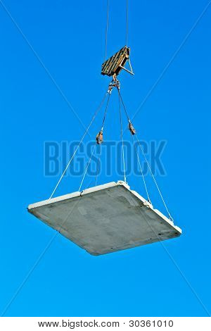 Elevating crane lifting a concrete plate